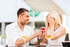 Happy couple with engagement ring and wine at cafe. Love, proposal, relations, people and holidays concept - happy couple with engagement ring in small red gift royalty free stock photography