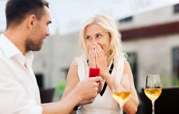 Happy couple with engagement ring and wine at cafe. Love, proposal, relations, people and holidays concept - happy couple with engagement ring in small red gift stock images