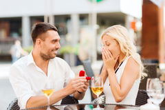 Happy couple with engagement ring and wine at cafe. Love, proposal, relations, people and holidays concept - happy couple with engagement ring in small red gift stock photo