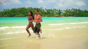 Happy couple enjoy honeymoon on the tropical beach at sunny summer day. Interracial couple white Caucasian man and tanned Asian girl close-up on tropical beach stock video footage