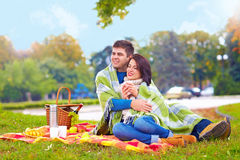 Happy couple enjoying autumn picnic in city park Stock Photo