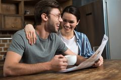 Happy couple enjoying breakfast with coffee and newspaper royalty free stock photography