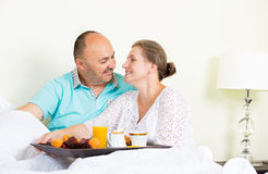 Happy couple enjoying breakfast, morning in a bed Stock Photography