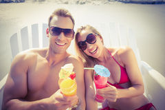 Happy couple enjoying cocktails on the beach. On a sunny day Royalty Free Stock Images