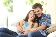 Happy couple enjoying in a couch at home Royalty Free Stock Image