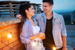 Happy couple enjoying drinks and balcony party. royalty free stock photo