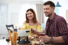 Happy couple enjoying fondue dinner stock photos
