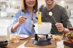 Happy couple enjoying fondue dinner at home royalty free stock photo