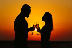 Happy couple enjoying a glass of wine or champagne, silhouette o. F couple in love drinking wine from wineglasses during romantic dinner at sunset on the beach stock image