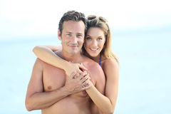 Happy couple enjoying holidays on the seaside. Portrait of middle-aged couple embracing by the beach Stock Images