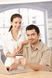 Happy couple enjoying online shopping smiling stock image