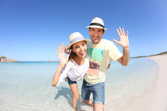 Happy couple enjoying on sandy beach. Happy couple walking in crystal clear sea water Royalty Free Stock Photo