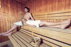 Happy couple enjoying the sauna together at the spa.  Stock Photos