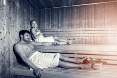 Happy couple enjoying the sauna together at the spa stock photos