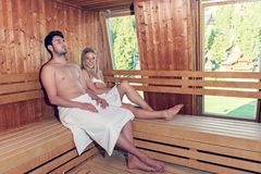 Happy couple enjoying the sauna together at the spa.  Stock Photography