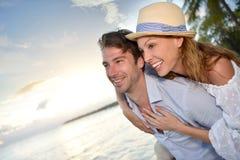 Happy couple enjoying by the seaside at sunset Stock Images