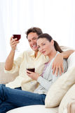 Happy couple enjoying their glasses of red wine Stock Photos