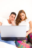 Happy couple enjoying using laptop computer in bed royalty free stock images