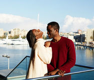 Happy couple enjoying vacation holiday outdoors. Portrait of smiling men and women standing on the balcony with beautiful yacht port background during their Royalty Free Stock Photography