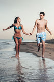 Happy couple enjoying vacations on the beach Stock Images
