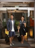 Happy couple entering hotel lobby Stock Images