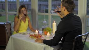 Happy Couple In The Evening For A Romantic Dinner, Clink Glasses And Drink Wine. Beauty couple in love for a romantic evening candlelight dinner. They clinked stock footage