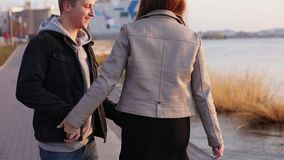 Happy couple on the evening walk at the lake. Girl leads boyfriend stock footage