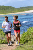 Happy couple excercising and jogging along the sea Royalty Free Stock Photo