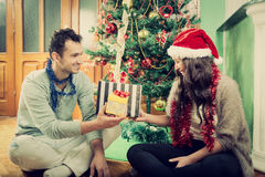 Happy couple exchanging gifts at home by Christmas tree royalty free stock photography