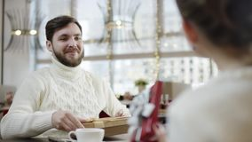 Happy couple exchanging gifts by table and looking inside them and man kissing feomale hand stock footage