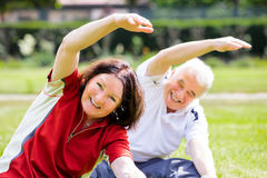 Happy Couple Exercising In Park Stock Image