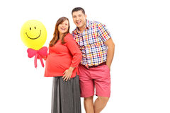 Happy couple expecting a baby and holding a balloon royalty free stock photo