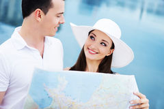 A happy couple exploring a map on the sea Stock Image