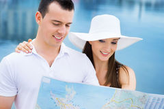 A happy couple exploring a map on the sea Royalty Free Stock Image