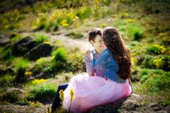 Happy couple face to face and Valentine`s Day. young couple sitting on the grass at sunset royalty free stock photo