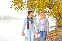 Happy couple in fall under leaves stock photography
