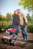 Happy couple of a family of farmers on their garden rejoice on a. Happy couple of a family of farmers on their garden rejoice Royalty Free Stock Images