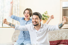 Happy couple feeling jubilant. Sense of jubilation. Content vivacious young couple rising their hands and smiling while celebrating victory stock image