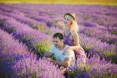 Happy couple in a field of lavender. A loving couple walks in the field of lavender, dreams and smiles. They are happy together and love each other stock images