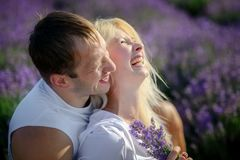 Happy couple in a field of lavender. A loving couple walks in the field of lavender, dreams and smiles. They are happy together and love each other royalty free stock image
