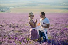 Happy couple in a field of lavender. A loving couple walks in the field of lavender, dreams and smiles. They are happy together and love each other stock photo