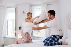 Happy couple fighting with pillows in bed stock image