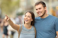 Happy couple finding location and pointing on the street. Happy couple finding location and pointing at side walking on the street Stock Photo