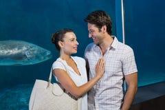 Happy couple beside the fish tank Royalty Free Stock Photos