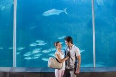 Happy couple beside the fish tank Royalty Free Stock Photo