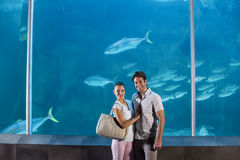 Happy couple beside the fish tank Royalty Free Stock Images