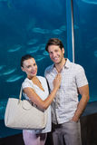Happy couple beside the fish tank Stock Images