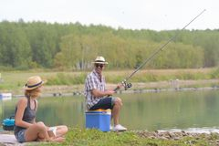 Happy couple fishing on banks pond. Happy couple fishing on the banks of the pond Royalty Free Stock Image