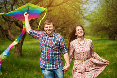 Happy couple are fling a kite on a spring meadow. Loving couple are fling a kite on a spring meadow stock photo