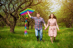 Happy couple are fling kite on a spring meadow. Loving couple are fling a kite on a spring meadow royalty free stock images